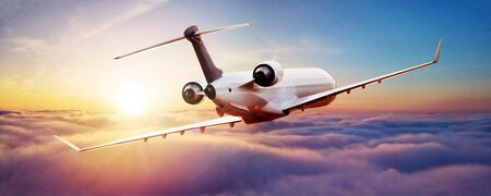 Private jet plane flying above clouds in beautiful sunset light. Modern and fastest mode of transportation, business life Banco de Imagens