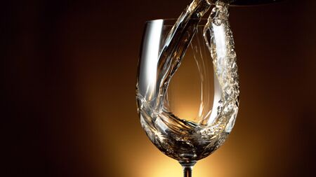 Detail of pouring white wine into glass, dark gradient background. Free space for text Stock fotó