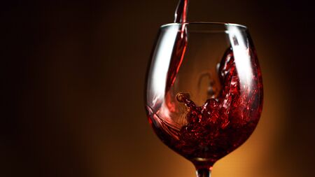 Detail of pouring red wine into glass, dark gradient background. Free space for text
