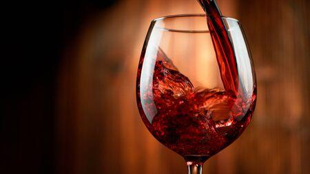 Detail van het gieten van rode wijn in glas, donkere houten achtergrond. Vrije ruimte voor tekst Stockfoto