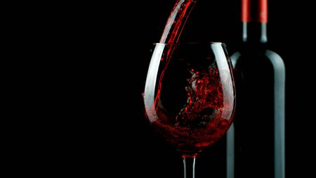Detail of pouring red wine into glass, isolated on black