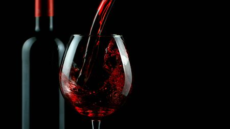 Detail of pouring red wine into glass, isolated on black Stock fotó