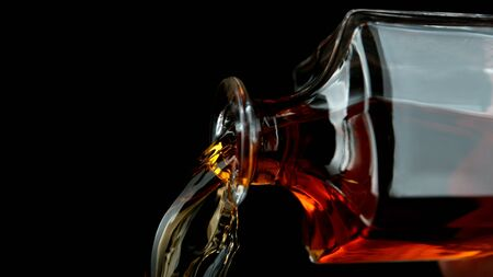 Detail of pouring whiskey from bottle, isolated on black background