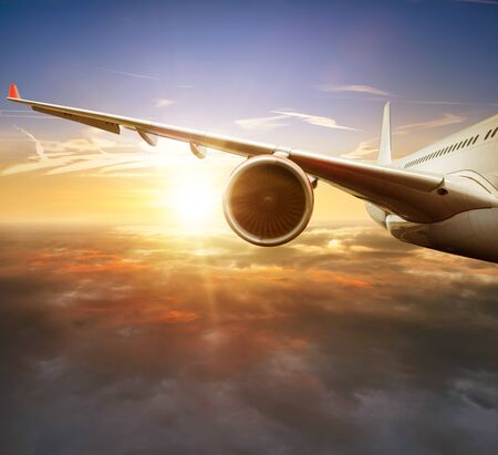 Detail of passengers commercial airplane wing flying above clouds in sunset light. Concept of fast travel, holidays and business. Banco de Imagens