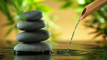 Un jet d'eau s'écoulant d'un tube de bambou, d'un spa et d'un concept de bien-être. Banque d'images