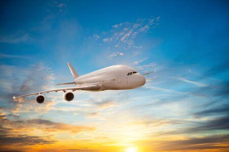 Passengers commercial airplane flying in sunset light 免版税图像