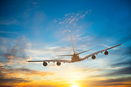 Passengers commercial airplane flying in sunset light. Banco de Imagens