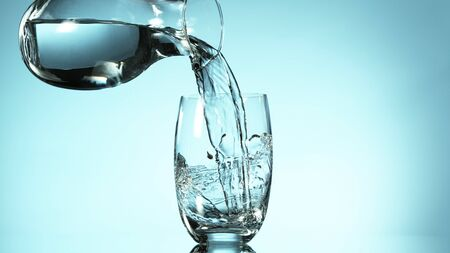 Freeze motion of pouring water from carafe into glass, free space for text