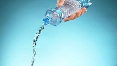 Freeze motion of pouring water from plastic bottle, free space for text Stock Photo
