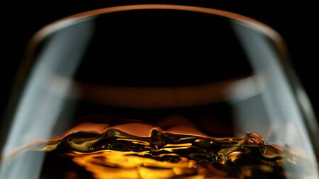 Detail of cognac in glass isolated on black background