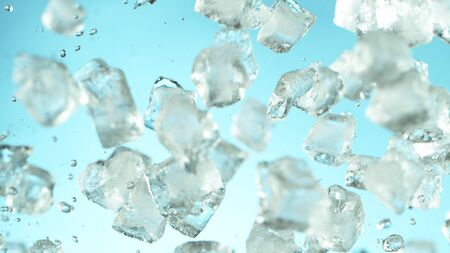Crushed ice explosion on blue background. Freeze motion of flying pieces of ice.