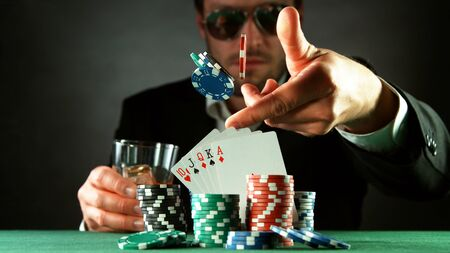 Poker player throwing chips. Concept of hazard gaming, poker chips on table
