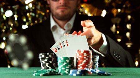 Poker player throwing chip. Concept of hazard gaming, poker chips on table