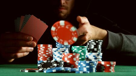 Poker player throwing red chip. Concept of hazard gaming, poker chips on table 写真素材