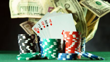 Falling US dollars banknotes in casino. Concept of hazard gaming, poker chips on table