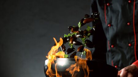 Closeup of chef throwing mussels from wok pan in fire. Fresh asian food preparation on dark background. 写真素材