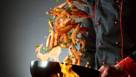 Closeup of chef throwing prawns from wok pan in fire. Fresh asian food preparation on dark background.