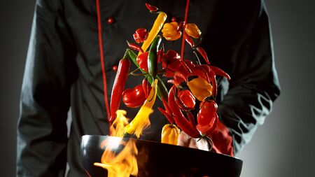 Closeup of chef throwing chilli peppers mix from wok pan in fire. Fresh asian food preparation on dark background. 写真素材