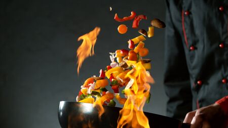 Closeup of chef throwing vegetable mix from wok pan in fire. Fresh asian food preparation on dark background. 写真素材