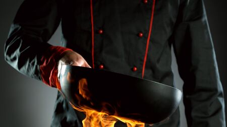 Closeup of chef holding empty wok pan in fire, ready to prepare for cooking. 写真素材