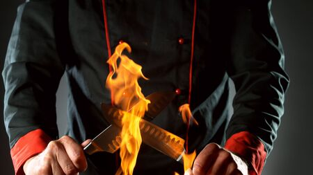 Closeup of chef holding knives in fire, ready to prepare for cooking.
