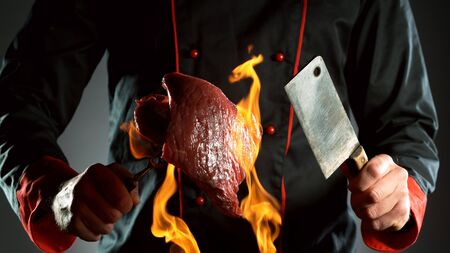 Closeup of chef holding cleaver and raw beef steak in fire, ready to prepare for cooking. 写真素材