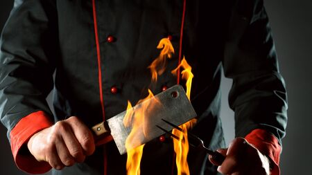 Closeup of chef holding cleaver and fork in fire, ready to prepare for cooking.