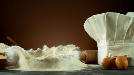 Freeze motion of falling yeast dough into flour. Ingredients for cooking, preparation concept with cooking cap.