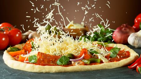 Falling mozzarella cheese on pizza, freeze motion. Italian traditional meal.