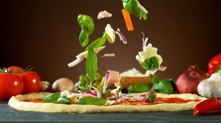 Falling raw ingredients on pizza, freeze motion. Italian traditional meal.