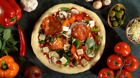 Top view of pizza meal preparation, raw ingredients around. Italian traditional meal.