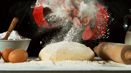 Freeze motion of cooker with clapping hands above yeast dough. Food preparation concept, ingredients around
