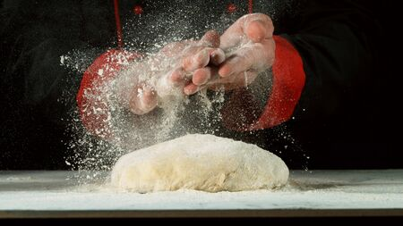 Freeze motion of cooker with clapping hands above yeast dough. Food preparation concept.