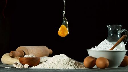 Freeze motion of falling raw egg into flour. Ingredients for cooking, food preparation concept. 写真素材