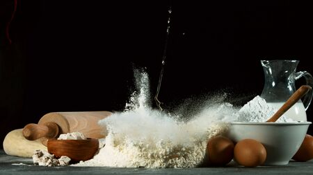Freeze motion of falling yeast dough into flour. Ingredients for cooking, food preparation concept. 写真素材
