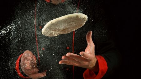 Freeze motion of cooker processing yeast pizza dough. Food preparation concept, ingredients around