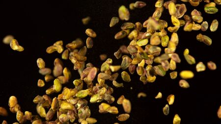 Realistic freeze motion of flying pistachios on black background.
