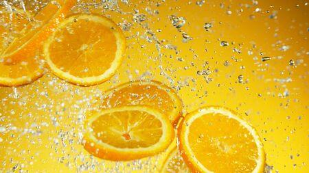 Freeze motion of flying orange pieces with water splashes. Studio shot of fresh summer beverage on soft orange background.