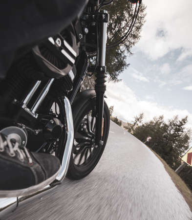 Driver riding motorcycle on an asphalt road in mountain, detail of front wheel, close-up.front, 版權商用圖片