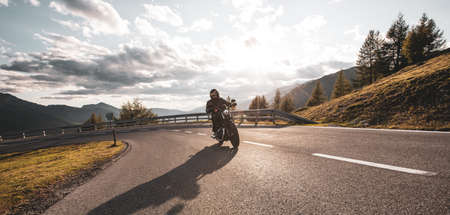 Motorcycle rider on the mountain road, wide format. Dramatic sunset sky 版權商用圖片