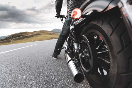 Driver riding motorcycle on an asphalt road in mountain, detail of rear wheel, close-up.front, 版權商用圖片