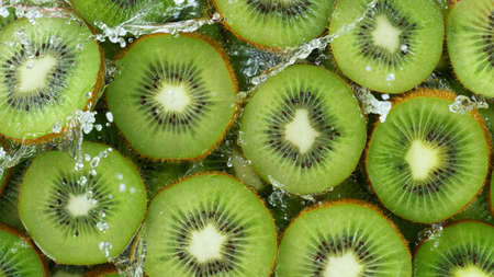 Top view of sliced kiwi with water splashes. Fresh juicy food and drink background.