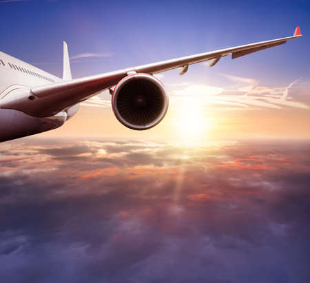 Detail of jetplane wing flying above clouds in sunset. Beautiful sunset scenery, transportation and fast travel concept.