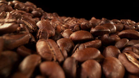 Pile of roasted cocoa beans, whole unpeeled pieces, free space for text.