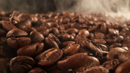 Pile of fresh roasted coffee beans with smoke around. Delicious coffee background