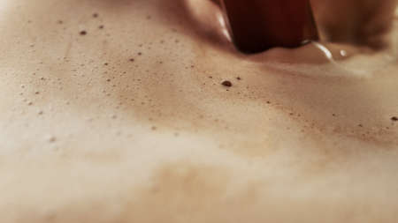 Detail of coffee drink being pour into foamy coffee drink. Abstract coffee background.