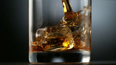 Pouring Glass of scotch whiskey and ice. Freeze motion of splashing liquid.