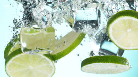 Fresh lime dropped into water with splash and ice cubes. Studio shot with clear background.