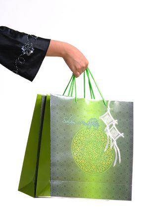 hand carrying green shopping bags