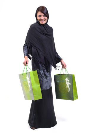 緑の買い物袋を運ぶ女性